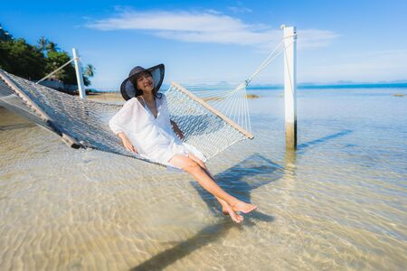 Portrait beautiful young asian woman sitting on hammock around sea beach ocean for relax in holiday vacation travel concept Stock Photo