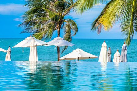 Beautiful luxury outdoor swimming pool with umbrella and chair and coconut palm tree Archivio Fotografico - 128371193