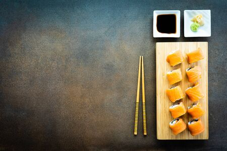Salmon fish meat sushi roll maki on wood plate with wasabi and soy sauce - Japanese food style Imagens