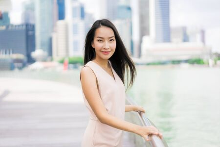 Beautiful asian woman smile and happy to travel in singapore city
