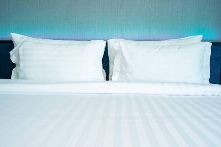 침실 내부에 조명 램프 장식이 있는 아름다운 고급스러운 편안한 흰색 베개 스톡 콘텐츠