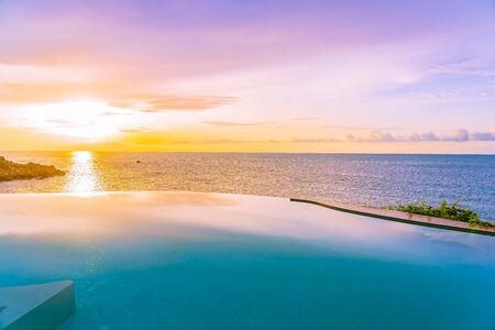 Beautiful outdoor infinity swimming pool  with sea ocean view and white cloud blue sky at sunrise time for holiday vacation and travel Archivio Fotografico - 128376297