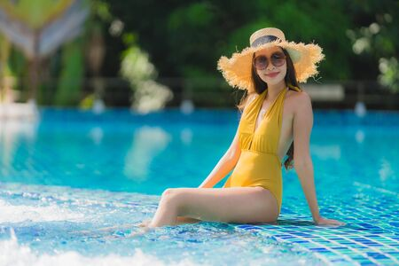 Portrait beautiful young asian woman leisure relax smile and happy around swimming pool in hotel resort for holiday vacation trip