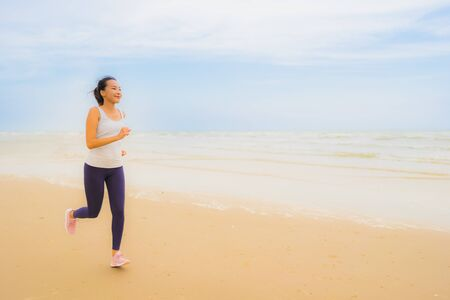 Portrait beautiful young sport asian woman exercise by run and jogging on the outdoor nature beach and sea for healthy 写真素材