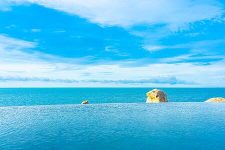 Beautiful outdoor infinity swimming pool with sea ocean view and white cloud blue sky for holiday vacation and travel Stockfoto - 128811841