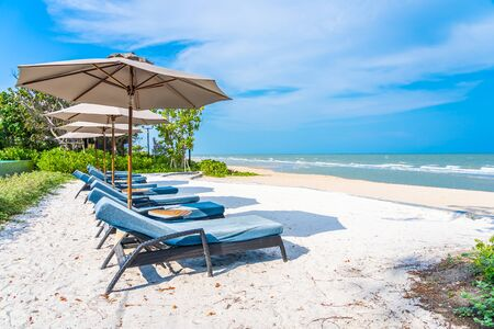 Umbrella and chair on the beach sea ocean with blue sky and white cloud for leisure travel and vacation 스톡 콘텐츠 - 128858340