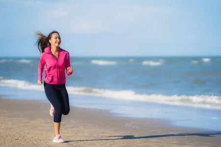 Schöne junge asiatische Frau des Porträts, die auf dem tropischen Naturstrand Meer Ozean für gesundes läuft und trainiert