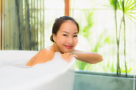 Portrait young beautiful asian woman take a bath in bathtub for leisure relax and in bathroom interior