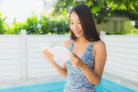 Portrait beautiful young asian woman happy smile with reading book around swimming pool in leisure vacation Stock fotó