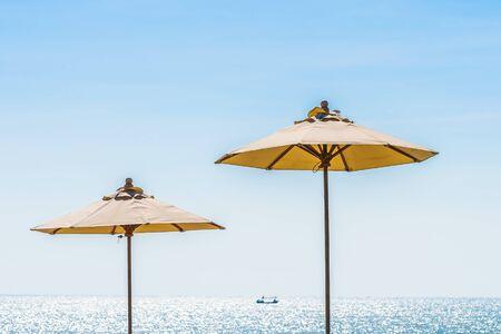 Hermoso paisaje de mar océano en el cielo con sombrilla y silla alrededor de la lujosa piscina al aire libre en el complejo hotelero para viajes de placer y vacaciones Foto de archivo