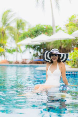 Portrait beautiful young asian woman smile happy relax around swimming pool in hotel resort for holiday vacation