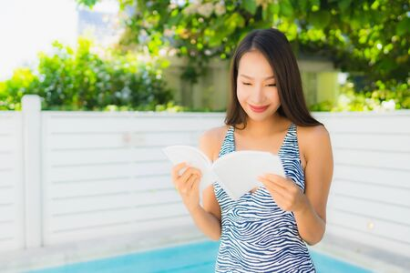 Portrait beautiful young asian woman happy smile with reading book around swimming pool in leisure vacation 版權商用圖片