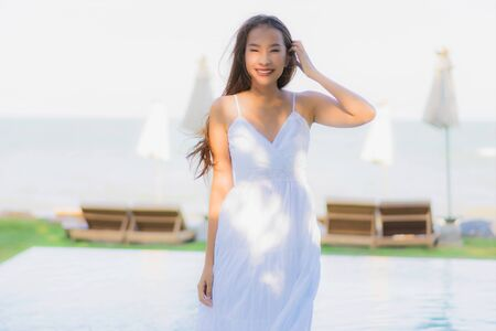 Portrait beautiful young asian woman happy smile and relax around swimming pool in hotel resort for leisure travel and vacation 版權商用圖片