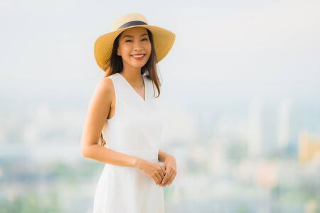 Portrait beautiful young asian woman happy smile relax on the roof top bar for leisure in holiday vacation 版權商用圖片
