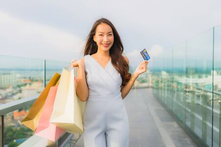Portrait beautiful young asian woman happy and smile with credit card for shopping bag from department store mall