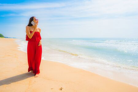 Portrait beautiful young asian woman using cellphone or mobile phone with walk on the beach and sea for leisure holiday vacation concept