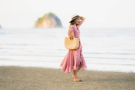 Portrait young beautiful asian woman walk smile and happy on the beach sea and ocean for leisure travel in holiday vacation