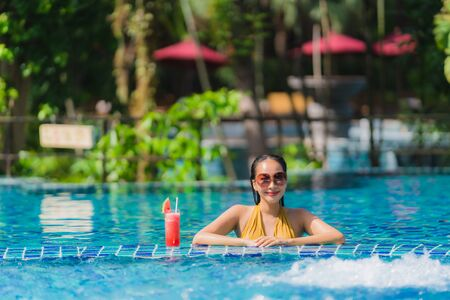 Portrait beautiful young asian woman leisure relax smile with watermelon juice around swimming pool in hotel resort for holiday vacation trip 版權商用圖片