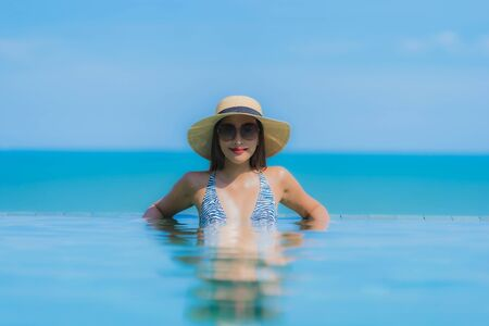 Portrait beautiful young asian woman happy smile relax in swimming pool at hotel resort neary sea ocean beach on blue sky for leisure travel in vacation
