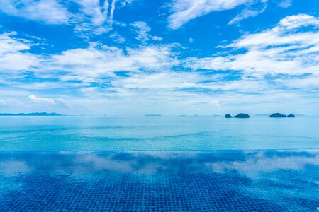 Beautiful outdoor swimming pool with sea ocean on white cloud blue sky background for holiday vacation travel concept