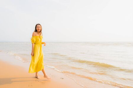 Portrait beautiful young asian woman walk on the beach and sea ocean with smile happy relax for leisure travel vacation at sunset time Stok Fotoğraf