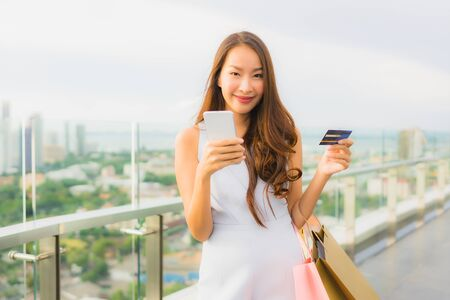 Portrait beautiful young asian woman happy and smile with credit card and mobile or smart phone and shopping bag from department store shop and mall 写真素材