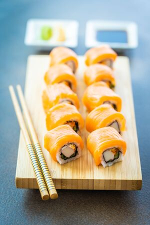 Salmon fish meat sushi roll maki on wood plate with wasabi and soy sauce - Japanese food style Stock Photo