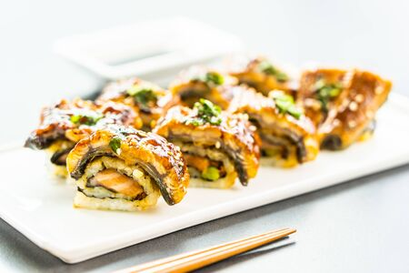 Grilled eel or unagi fish with salmon and vegetable inside sushi maki roll and sweet sauce on white plate - Japanese food style Фото со стока