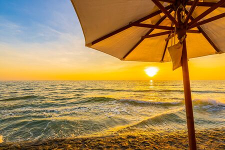 Umbrella and chair with pillow around beautiful landscape of beach and sea at sunrise or sunset time for holiday vacation and travel Фото со стока