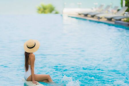 Portrait young asian woman happy smile relax around swimming pool in hotel resort for travel in holiday vacation concept