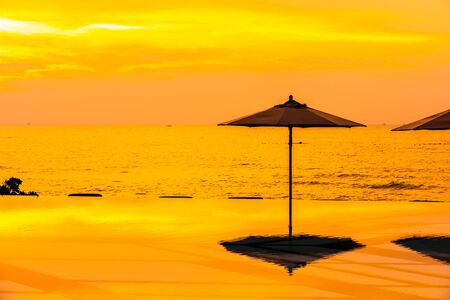 Umbrella and chair around swimming pool neary sea ocean beach at sunrise or sunset time for leisure travel and vacation Фото со стока