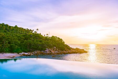Beautiful outdoor infinity swimming pool in hotel resort with sea ocean view and white cloud blue sky at sunrise time for holiday vacation and travel