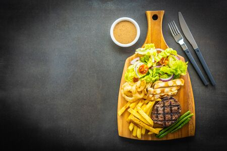 Grilled beef meat steak with french fries sauce and fresh vegetable on wooden cutting board