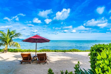 Beautiful landscape of beach sea ocean with empty chair deck and umbrella nearly coconut palm tree with white cloud and blue sky for leisure travel in holiday vacation