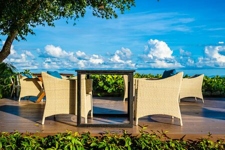 Empty table and chair for dining set nearly sea ocean beach on white cloud blue sky background