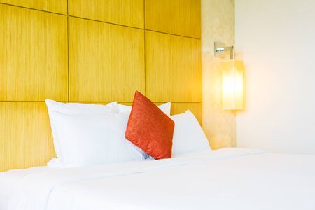 White comfortable pillow on bed decoration in hotel bed room interior Фото со стока