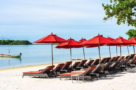 Beautiful outdoor tropical beach sea ocean with umbrella chair and lounge deck around there on white cloud blue sky background for holiday vacation travel Фото со стока
