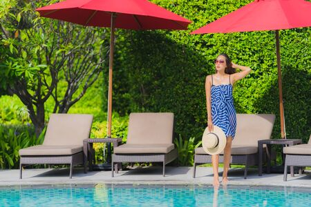 Portrait young asian woman relax smile happy around outdoor swimming pool in hotel resort with sea ocean view in holiday vacation concept 版權商用圖片