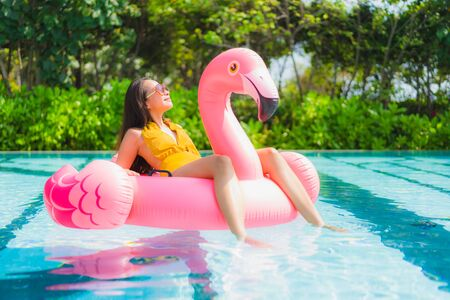 Portrait beautiful young asian woman on the flamingo inflatable float in swimming pool at hotel resort for leisure holiday vacation concept