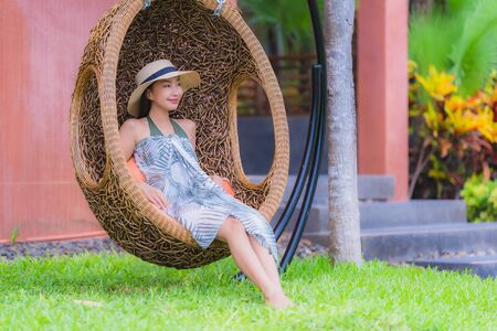 Portrait young asian woman sitting on swing chair in the garden with smile and relax