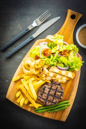 Grilled beef meat steak with french fries sauce and fresh vegetable on wooden cutting board Stock Photo - 129838120