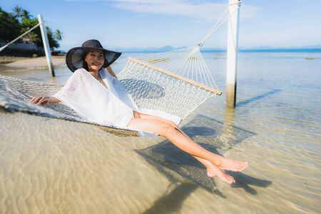 Portrait beautiful young asian woman sitting on hammock around sea beach ocean for relax in holiday vacation travel concept Reklamní fotografie