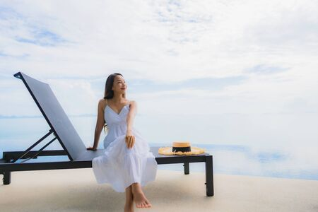 Portrait young asian woman relax smile happy around swimming pool in hotel and resort for holiday vacation travel concept Zdjęcie Seryjne - 130031868