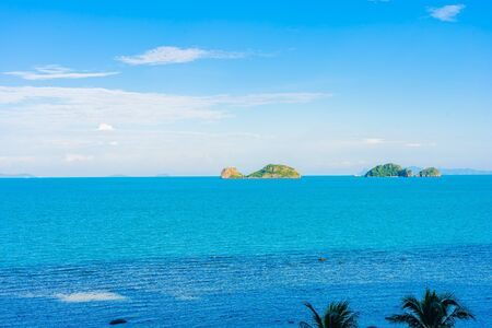 Beautiful outdoor beach sea ocean with coconut palm and other tree around island for travel in holiday vacation concept