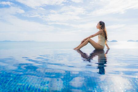 Portrait young asian woman relax smile happy around swimming pool in hotel and resort for holiday vacation travel concept Zdjęcie Seryjne - 130026904