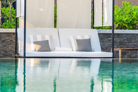 Outdoor swimming pool with umbrella chair lounge around there for leisure travel and vacation concept