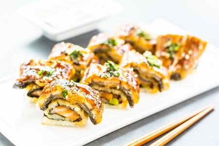 Grilled eel or unagi fish with salmon and vegetable inside sushi maki roll and sweet sauce on white plate - Japanese food style Stock Photo