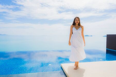 Portrait young asian woman relax smile happy around swimming pool in hotel and resort for holiday vacation travel concept Zdjęcie Seryjne - 130027210