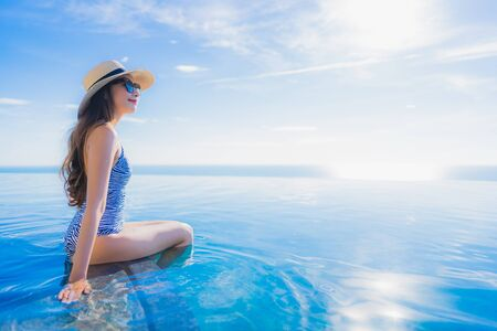 Portrait beautiful young asian woman smile happy relax around swimming pool in hotel resort with sea and ocean view for leisure travel in holiday vacation