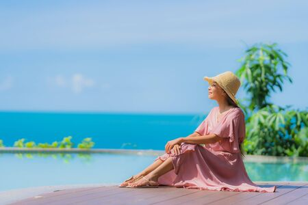 Portrait young asian woman relax smile happy around outdoor swimming pool in hotel resort with sea ocean view in holiday vacation concept Stock fotó